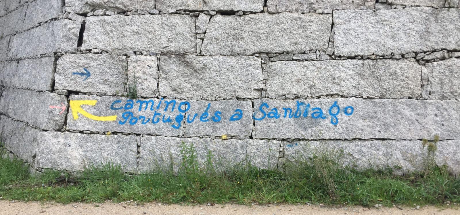 evia yoga reiki solingen jakobsweg camino pilgern steinwand mit spruehschrift camino portugues a santiago